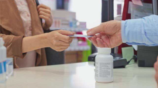 LD Female customer paying with a contactless card at the drugstore
