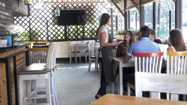 Female customer raising hand so her group can order dinner video