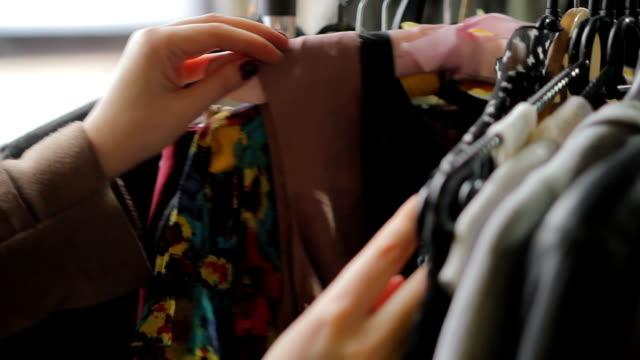 vídeos de stock, filmes e b-roll de cliente feminino classificação cabides com roupas, escolhendo roupas para comprar na loja - arméria