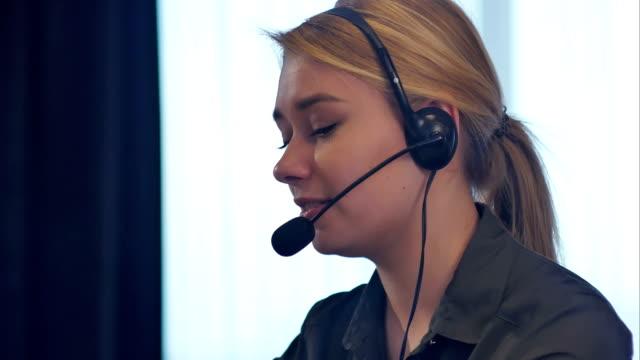 vídeos y material grabado en eventos de stock de operador de soporte al cliente mujer con auriculares hablando y sonriendo - centro de llamadas