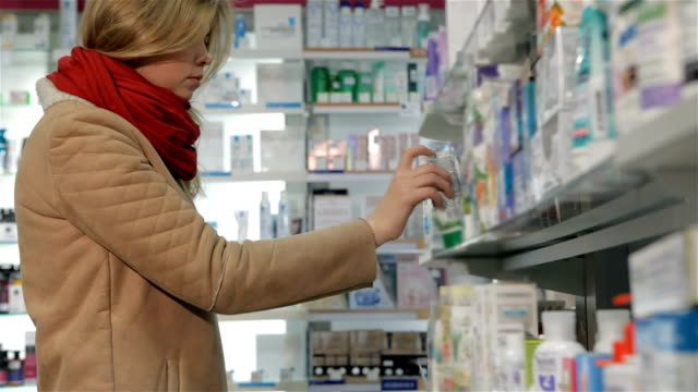 Female customer takes ointment from shelf at the drugstore video