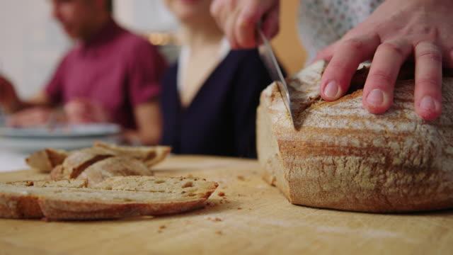 vídeos y material grabado en eventos de stock de rebanadas de pan de corte femeninapara servir a los amigos en la cena - cuchillo cubertería