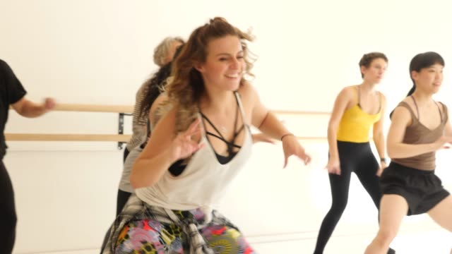 Female dancer teaching students in dance class