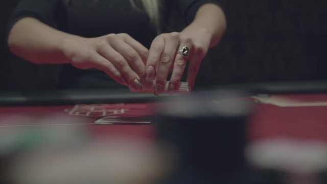 Female dealer's hands shuffle poker cards skillfully during a game at the camera video