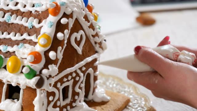 weibliche schmückt ein lebkuchenhaus mit einer creme in den spritzbeutel - lebkuchenhaus stock-videos und b-roll-filmmaterial