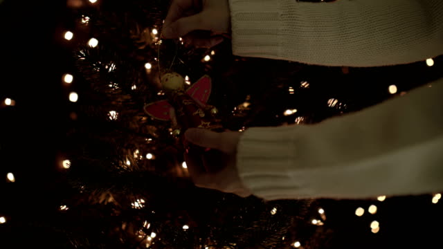 Female decorating the fairy garland on a Christmas tree with bokeh lights background video