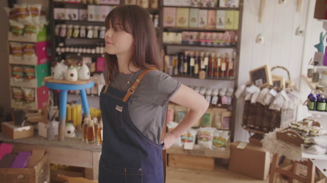 vídeos de stock e filmes b-roll de female deli owner tying apron and standing arms crossed in store - avental
