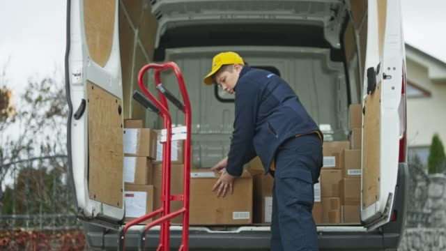 Female delivery service driver placing packages onto the cart