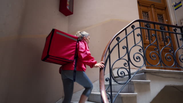 female delivery worker on steps in residential building searching for customer's apartment - food delivery filmów i materiałów b-roll