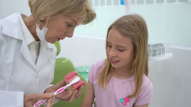 Female dentist explaining to little girl how to brush her teeth properly during consult
