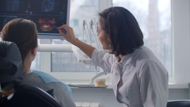 bir kadın diş hekimi ekranda mri görüntüsü ve hastanın dişlerinin röntgenini gösterir. tedavi planı ve sağlıklı gülümseme tartışma. kaza sonrası iyileşme - diş sağlığı stok videoları ve detay görüntü çekimi