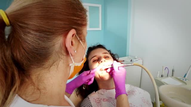 女性歯科医が女の子の歯にタービン ドリルを使用します。 - 歯科医師点の映像素材/bロール