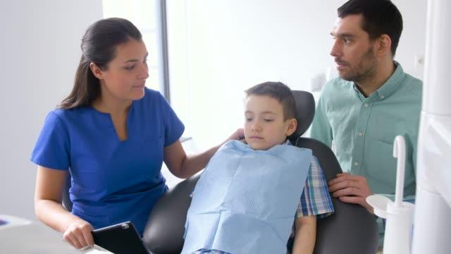 vídeos de stock, filmes e b-roll de dentista feminina com paciente criança na clínica odontológica - sul europeu