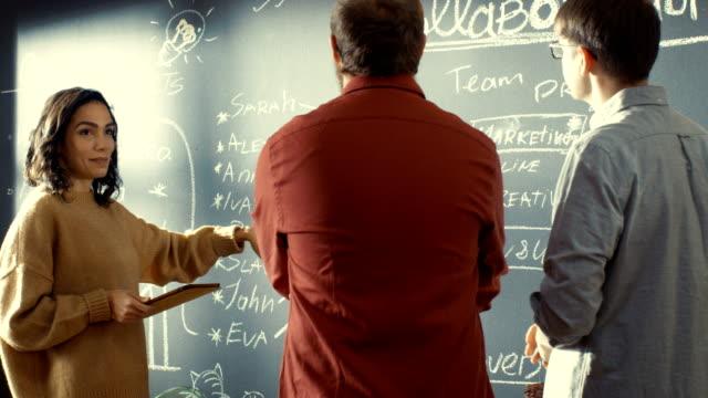 Développeur féminin avec tablette ordinateur pourparlers avec programmeur et chef de projet, ils utilisent Blackboard mur comme un planificateur. Ils travaillent dans le Bureau de style créatif. - Vidéo