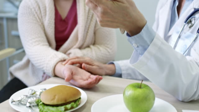 Female Dietician Checking Pulse of Schoolgirl Tilt up of dietician in lab coat checking pulse of schoolgirl during consultation about healthy food choices; green apple, burger and glucose meter lying on table nutritionist stock videos & royalty-free footage
