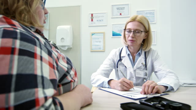 female dietician talking to overweight patient - sovrappeso video stock e b–roll