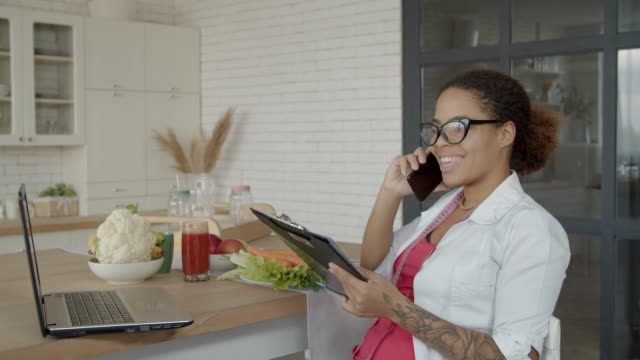 Female dietitian consulting patient on cellphone Positive professional african american female dietitian in uniform holding clipboard and discussing personalized diet plan with patient using cellphone at workplace, expressing friendliness and care. nutritionist stock videos & royalty-free footage