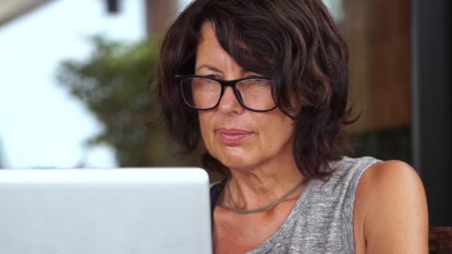 Female digital nomad using laptop outdoors