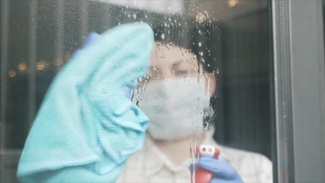 Female disinfecting glass door at home. Young woman cleaning the windows at home using cleaning products. She is keeping all the surfaces virus free. cleaning stock videos & royalty-free footage