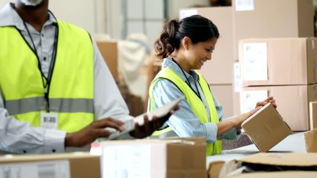 weibliche verteilung lagermitarbeiter bereitet zu senden, kundenauftrag - philippinischer abstammung stock-videos und b-roll-filmmaterial