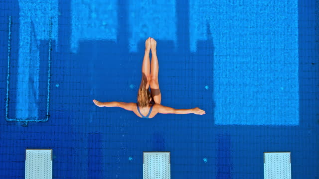 slo mo cs female diver diving into the blue pool and rotating in the air - tuffarsi video stock e b–roll