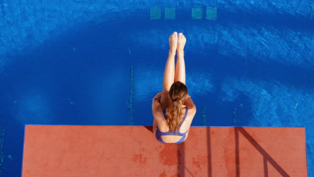 SLO MO CS Female diver holding her legs up while sitting on the edge of the diving platform and diving into the pool