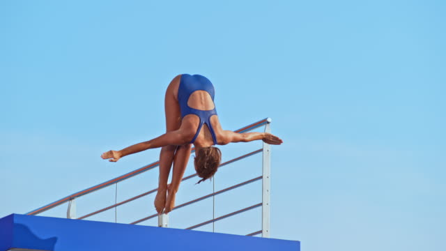 slo mo female diver jumping into the pool - tuffarsi video stock e b–roll