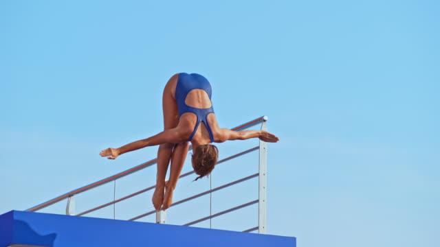 slo mo weibliche taucher springen in den pool - sprung wassersport stock-videos und b-roll-filmmaterial
