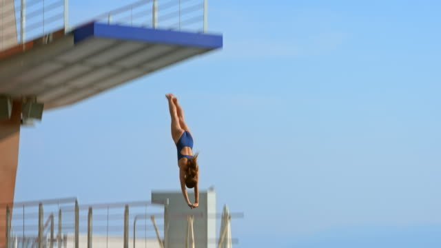 slo mo female diver jumping off the sunny diving platform - tuffarsi video stock e b–roll