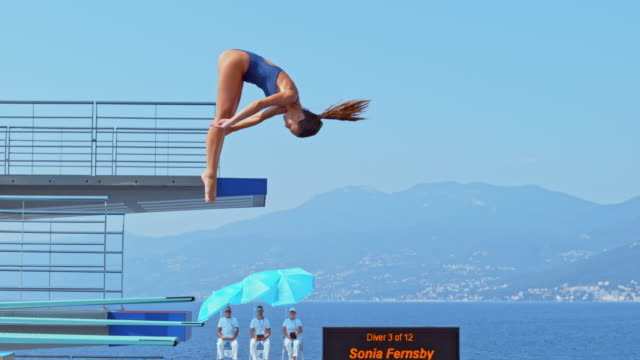 SLO MO Female diver rotating while diving into the pool at a competition Slow motion wide handheld shot of a female high diver rotating in the air while diving into the pool at a competition. Shot in Croatia. perfection stock videos & royalty-free footage
