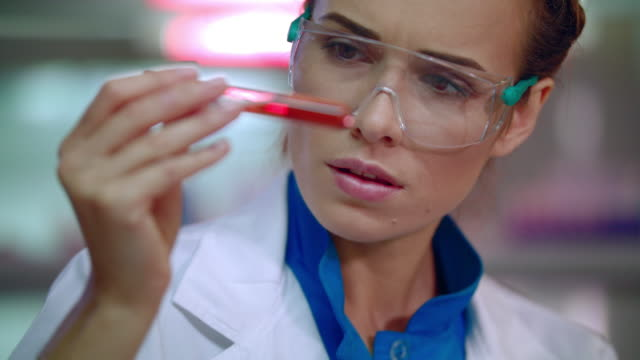 Female doctor analyzing liquid in test tube. Lab doctor doing medical research video