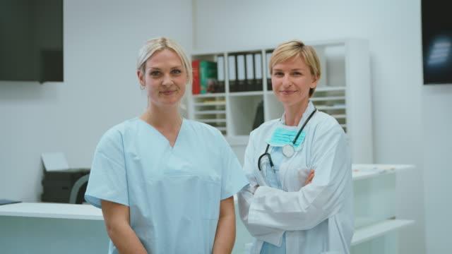 vídeos de stock e filmes b-roll de female doctor and nurse standing in hospital lobby - enfermeira