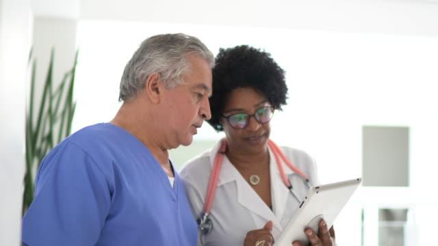 vidéos et rushes de docteur et infirmière féminin marchant et utilisant la tablette numérique à l'hôpital - infirmier