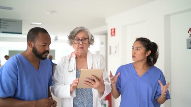 vidéos et rushes de docteur et infirmières féminins marchant et parlant à l'hôpital - infirmier