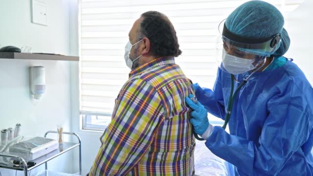 ärztin überprüft eine ältere patientin mit allen schutzmaßnahmen aufgrund der covid-19-pandemie - lateinische schrift stock-videos und b-roll-filmmaterial