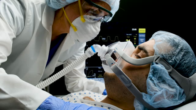 Female doctor checking on Covid-19 infected patient while connected to a ventilator