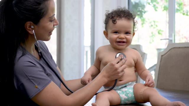 Female doctor check's baby's heart rate A female doctor of Hispanic descent is doing a routine check-up on a baby. The medical professional is using a stethoscope to check the child's heart rate. The baby is seated on a medical exam table. The doctor is smiling warmly at her patient. general practitioner stock videos & royalty-free footage