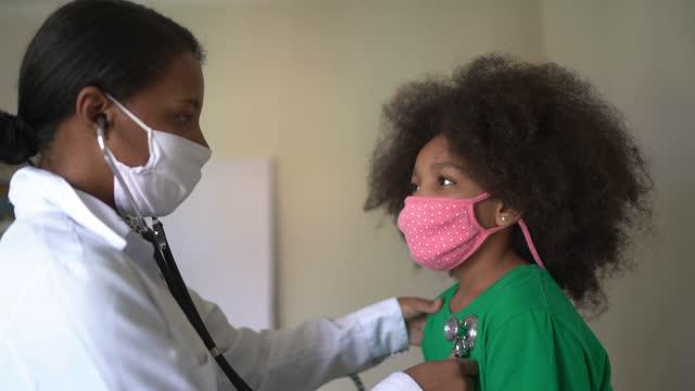medico donna controlla battito cardiaco di una bambina - clinica medica video stock e b–roll