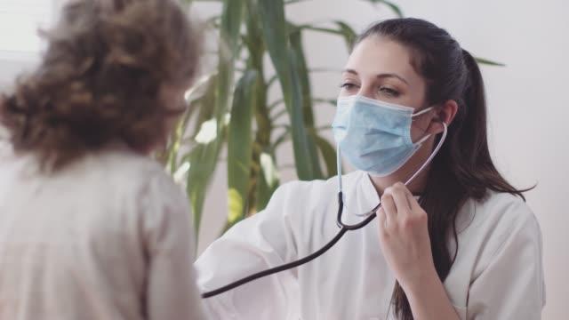 女性医師は、小さな女の子のストックビデオのハートビートをチェックします - 聴診器点の映像素材/bロール