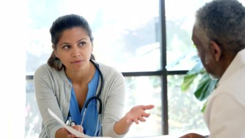 vídeos de stock e filmes b-roll de female doctor discusses diagnosis with senior male patient - doutor