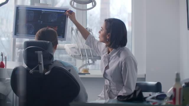 en kvinnlig läkare diskuterar med patienten en plan för återhämtning och rehabilitering av ansiktet efter olyckan - two dentists talking bildbanksvideor och videomaterial från bakom kulisserna