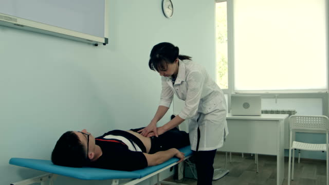 Female doctor doing abdominal examination on male patient video