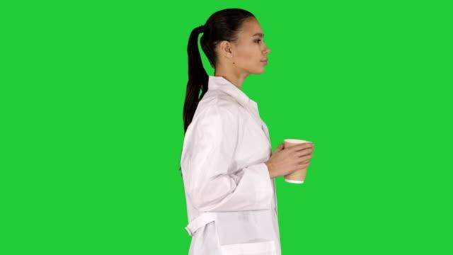 weiblicher arzt, der kaffee trinkt und auf einem grünen bildschirm läuft, chroma key - blickwinkel der aufnahme stock-videos und b-roll-filmmaterial