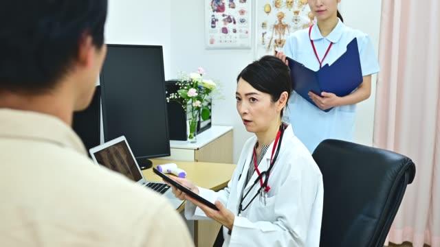 男性患者を診察する女性医師 - 聴診器点の映像素材/bロール