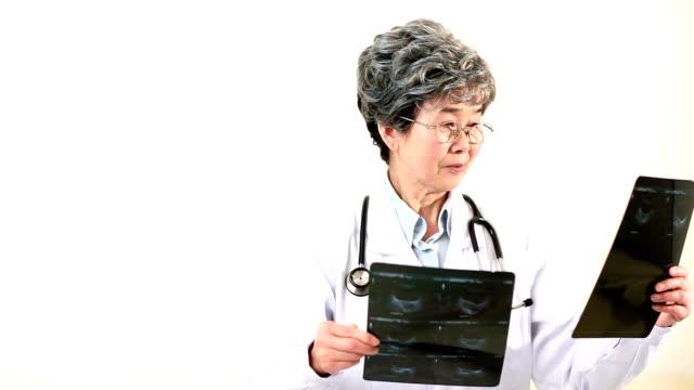 female doctor examining an x-ray, smiling - mature women studio grey hair bildbanksvideor och videomaterial från bakom kulisserna