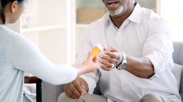 Female doctor gives prescription medication to male patient