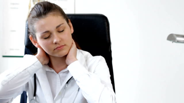 Female doctor has neck ache in office - tracking shot video