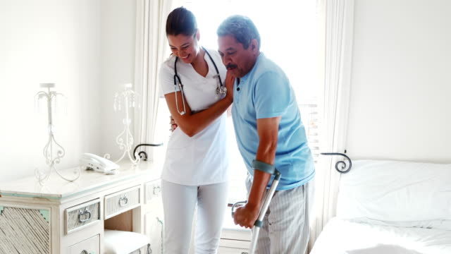 Female doctor helping senior man to walk with walker 4k Female doctor helping senior man to walk with walker in bedroom 4k crutch stock videos & royalty-free footage