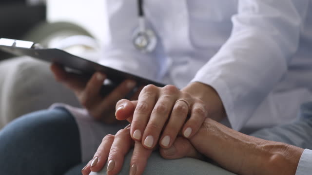 Female doctor holding hand of senior grandmother patient, closeup view