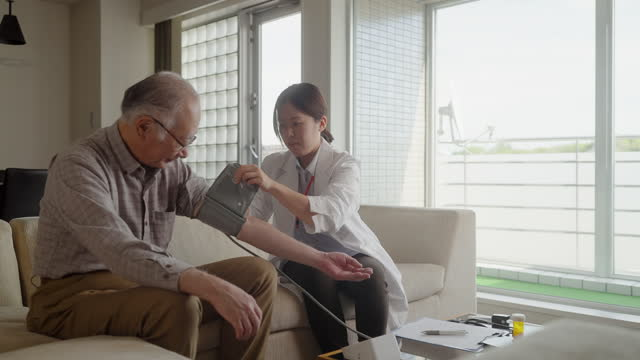 Female doctor home visiting senior man patient at his home